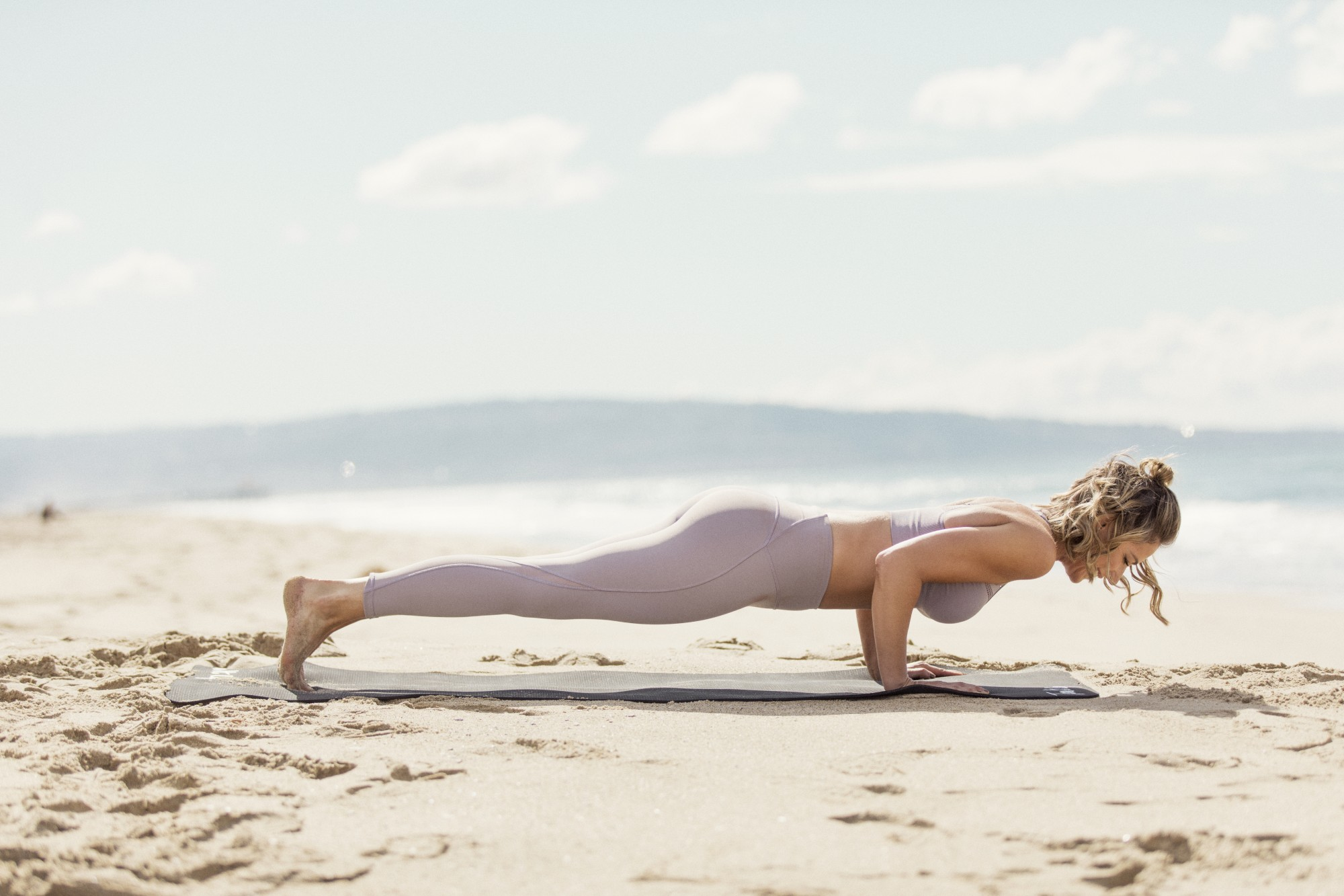 Karena Dawn from Tone It Up demonstrates proper from for a chaturanga pose in a yoga vinyasa flow.